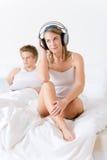 Los pares jovenes se relajan en cama con música y la computadora portátil Imagen de archivo libre de regalías