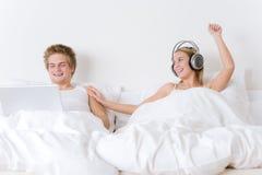 Los pares jovenes se relajan en cama con música y la computadora portátil Foto de archivo