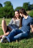 Los pares jovenes se relajan en parque Foto de archivo libre de regalías