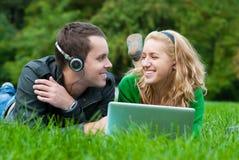Los pares jovenes se relajan y escuchan la música Fotografía de archivo libre de regalías