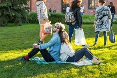 Los pares jovenes se sientan de nuevo a la parte posterior en el césped en el parque con los ojos cerrados y escuchan la música Foto de archivo libre de regalías