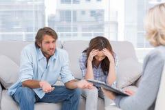 Los pares jovenes se sientan en el sofá del terapeuta Imagenes de archivo