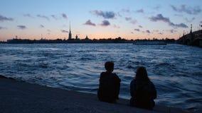Los pares jovenes se sientan en un terraplén del río de Neva en el backgro de Peter y de Paul Fortress Fotos de archivo