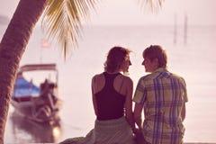 Los pares jovenes se sientan juntos debajo de una palmera y de la mirada hacia s Fotografía de archivo