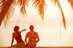 Los pares jovenes se sientan juntos debajo de una palmera y de la mirada hacia s Fotos de archivo libres de regalías