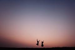 Los pares jovenes siluetean el salto al aire libre en la puesta del sol dramática Fotografía de archivo
