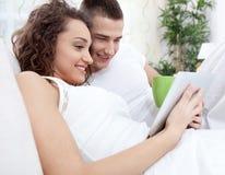 Los pares jovenes sonrientes que mienten en la cama y el uso hacen tabletas la PC Imagen de archivo