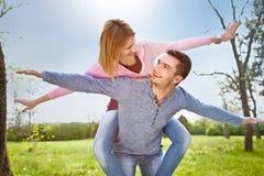 Los pares jovenes sonrientes tienen una fan al aire libre en parque de la primavera Fotografía de archivo libre de regalías