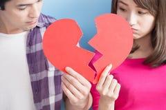 Los pares jovenes toman el corazón quebrado imagen de archivo libre de regalías
