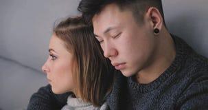 Los pares jovenes tristes se sientan juntos en el sofá y el abrazo almacen de metraje de vídeo
