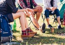 Los pares jovenes y el amigo que se sientan en silla discuten juntos en la leva Fotografía de archivo
