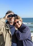 Los pares jubilados en la playa vacation con el abrazo de los prismáticos Foto de archivo