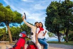 Los pares libres felices de la libertad que conducen la vespa emocionada el vacaciones de verano vacation Fotos de archivo
