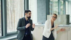 Los pares lindos de los colegas hombre y de los trajes que llevan de la mujer están bailando en la oficina que se divierte juntos metrajes