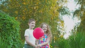Los pares lindos del amigo con el corazón hinchan en parque del verano almacen de video