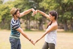 Los pares lindos en el parque que hace el corazón forman Fotografía de archivo libre de regalías
