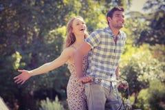 Los pares lindos en una bici montan en el parque Fotos de archivo libres de regalías