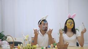 Los pares lindos y adorables volvieron a la niñez El hombre está sosteniendo dos huevos en sus manos y una mujer está sosteniendo