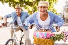 Los pares maduros felices que van para una bici montan en la ciudad Imagen de archivo libre de regalías