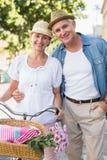 Los pares maduros felices que van para una bici montan en la ciudad Imágenes de archivo libres de regalías