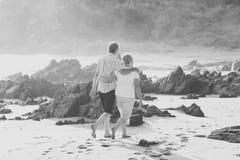 Los pares maduros mayores preciosos en su 60s o 70s retiraron caminar feliz y relajado en orilla de mar de la playa en el envejec Imagen de archivo