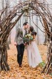Los pares maravillosos de la boda miran cariñosamente uno a debajo del arco pardo en bosque del otoño Fotografía de archivo