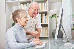 Los pares mayores aprenden sobre los ordenadores foto de archivo