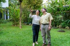 Los pares mayores asiáticos están caminando dentro del patio trasero fotografía de archivo
