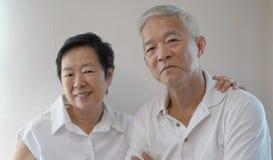 Los pares mayores asiáticos felices en el fondo blanco aman y abrazan Foto de archivo libre de regalías