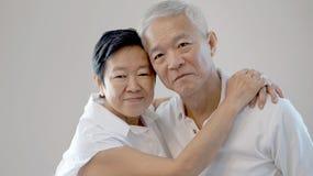 Los pares mayores asiáticos felices en el fondo blanco aman y abrazan Fotos de archivo libres de regalías