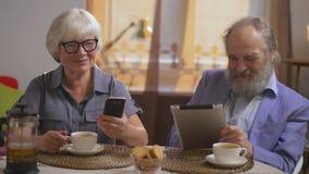 Los pares mayores beben té en su comedor que se sienta en una tabla con los artilugios metrajes