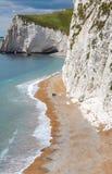 Los pares mayores caminan abajo de la playa y de los altos acantilados en Dorset, inglesa Foto de archivo