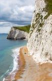Los pares mayores caminan abajo de la playa y de los altos acantilados en Dorset, inglesa Imagen de archivo libre de regalías
