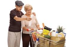 Los pares mayores chocados que miran una tienda acusan recibo Imágenes de archivo libres de regalías