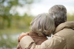 Los pares mayores con el suyo apoyan el abarcamiento en parque del otoño Fotografía de archivo