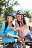 Los pares mayores con la correspondencia en la bici del país montan Imagenes de archivo