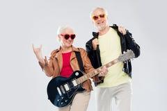Los pares mayores con la guitarra que muestra la mano de la roca firman Imágenes de archivo libres de regalías