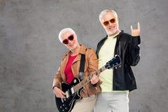 Los pares mayores con la guitarra que muestra la mano de la roca firman Foto de archivo libre de regalías