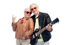Los pares mayores con la guitarra que muestra la mano de la roca firman Fotos de archivo libres de regalías
