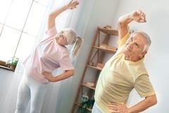 Los pares mayores ejercitan junta en casa la sonrisa gimnástica de la atención sanitaria alegre Foto de archivo