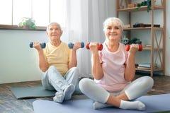 Los pares mayores ejercitan juntas en casa atención sanitaria levantan para arriba pesas de gimnasia Foto de archivo