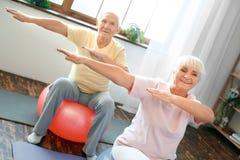 Los pares mayores ejercitan juntas en casa haciendo las manos de los aeróbicos a un lado Foto de archivo