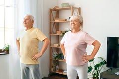 Los pares mayores ejercitan juntas en casa las manos de la atención sanitaria en la cintura lista Foto de archivo