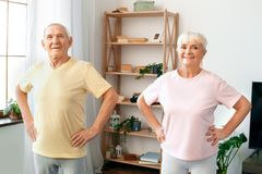 Los pares mayores ejercitan juntas en casa las manos de la atención sanitaria en la cintura que mira la cámara Imagenes de archivo