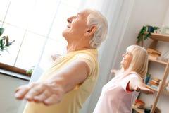 Los pares mayores ejercitan juntas en casa las manos gimnásticas de la atención sanitaria a un lado Fotografía de archivo libre de regalías
