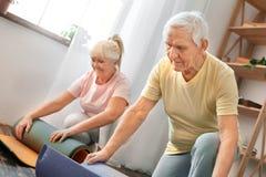 Los pares mayores ejercitan junto en casa el pensamiento de la estera de la yoga del balanceo de la atención sanitaria Imagenes de archivo