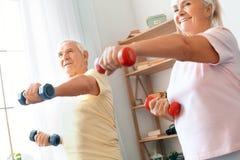 Los pares mayores ejercitan juntos en casa atención sanitaria con pesas de gimnasia en frente Fotografía de archivo libre de regalías