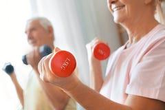 Los pares mayores ejercitan juntos en casa el primer de las pesas de gimnasia de la atención sanitaria Imagen de archivo