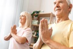 Los pares mayores ejercitan juntos en casa el primer del namaste de la atención sanitaria Imagen de archivo libre de regalías