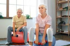 Los pares mayores ejercitan juntos en casa haciendo aeróbicos con los dubbells abajo Fotografía de archivo libre de regalías